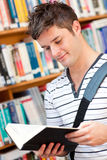 Cute male student reading a book. In a bookstore Royalty Free Stock Photos