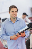 Cute male teacher holding some files while posing in his classroom Stock Photography