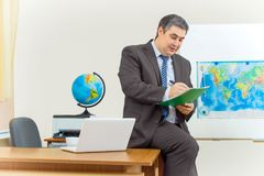 A cute male teacher sits on a desk in the classroom. He writes notes in a workbook Royalty Free Stock Photo