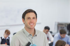 Cute male teacher standing in his classroom. Smiling at camera Royalty Free Stock Photos