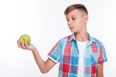 Cute male teenager is eating healthy food. Beautiful boy is holding an apple and looking at it with appetite. He is standing in colored shirt. Isolated on Stock Photography