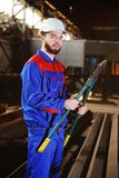 Cute man with a bolt cutter in his hands. Huge bolt cutter in the hands of a young handsome builder or worker in a helmet Stock Photography