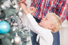 Cute man and child are preparing for New Year. Pretty small boy and his father are decorating Christmas tree. The father is giving a toy ball to his son. The royalty free stock photo