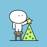 Cute man and Christmas tree. Cute funny man on the stool decorates Christmas tree with lights and the star on the blue background. Xmas and new year holidays Royalty Free Stock Photo