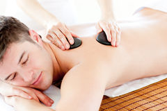Cute man enjoying a back massage with hot stones Royalty Free Stock Photography