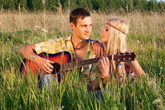 Cute man and fine woman sit on meadow Stock Photo