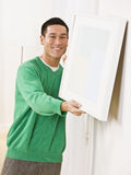 Cute man hanging canvas on Apartment Wall Royalty Free Stock Images