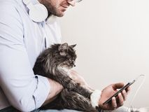 Cute man and cute kitten. Cute man wearing glasses with headphones and a mobile phone on a white background, gently hugging a cute kitten. People, pets, care Stock Photo