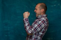 Cute man posing on blue background. Side view of happy man in plaid shirt is pleased and raises his hands up on blue background. Copy space Stock Image