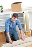 Cute man rolling a carpet out Stock Photos