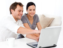 Cute man showing something on the laptop screen. To his girlfriend in the living room Royalty Free Stock Photography