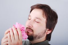 Cute man smeling pink roses Stock Photos