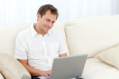 Cute man surfing on the web on the sofa Royalty Free Stock Images
