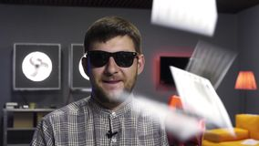 Cute man vlogger speaks and holds plastic gun spitting out dollar banknotes. Young bearded male vlogger wearing sunglasses and checkered shirt, joyfully speaks stock video footage