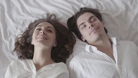 Cute man and woman falling on the bed and looking at each other with love. Young couple lying in the bed. Tender. Portrait of happy man and woman falling on the stock footage