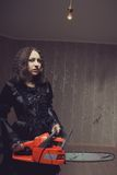 Cute maniac girl. Pretty cute red-eyed girl with bloody chainsaw posing in the empty room royalty free stock photography