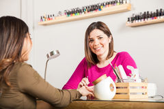 Cute manicurist working at a nail salon Stock Images