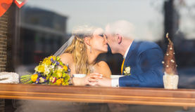Cute married couple in cafe, groom kissing a bride. Pure tenderness. Royalty Free Stock Photography