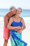 Cute mature couple embracing on the beach Stock Photo