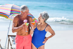 Cute mature couple having cocktails on the beach Stock Photography