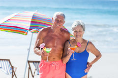 Cute mature couple having cocktails on the beach Stock Photo