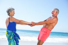 Cute mature couple holding hands on the beach Stock Photo