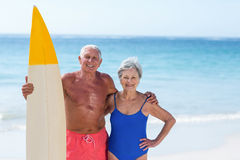 Cute mature couple holding a surfboard. On the beach Stock Image