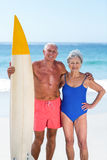 Cute mature couple holding a surfboard. On the beach Royalty Free Stock Photography