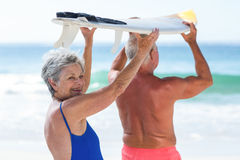 Cute mature couple holding a surfboard. On the beach Stock Photography