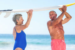 Cute mature couple holding a surfboard. On the beach Stock Photos