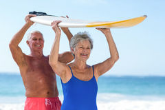 Cute mature couple holding a surfboard over their heads. On the beach Stock Photo