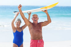 Cute mature couple holding a surfboard over their heads. On the beach Royalty Free Stock Image