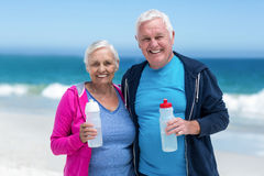 Cute mature couple holding water bottle Stock Photography