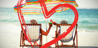 Cute mature couple lying on deckchairs Stock Images