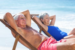 Cute mature couple lying on deckchairs Royalty Free Stock Photography