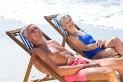 Cute mature couple lying on deckchairs Stock Photos