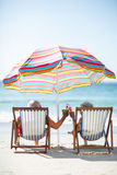 Cute mature couple lying on deckchairs Stock Photography