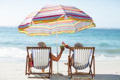Cute mature couple lying on deckchairs Royalty Free Stock Image