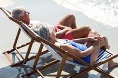 Cute mature couple lying on deckchairs Stock Image