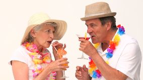 Cute mature couple sipping cocktails. Against a white background stock footage
