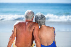 Cute mature couple sitting on the beach looking at the sea Royalty Free Stock Photography