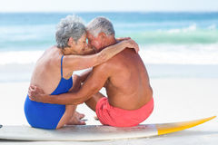 Cute mature couple sitting on a surfboard. On the beach Stock Images