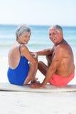 Cute mature couple sitting on a surfboard. On the beach Stock Photos