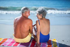 Cute mature couple sitting on a towel on the beach. On a sunny day Royalty Free Stock Photography