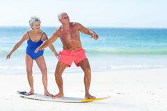 Cute mature couple standing on a surfboard. On the beach Royalty Free Stock Photo