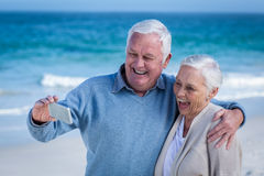 Cute mature couple taking selfie on the beach Stock Photography