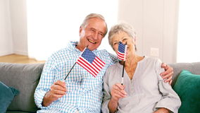 Cute mature couple waving american flags in the living room. In slow motion stock video