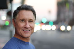 Cute mature man in the big city. Cute elder man in the big city royalty free stock photos