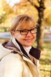 Cute mature woman in autumn park Stock Photos