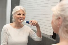 Electric toothbrush used by senior woman stock photos